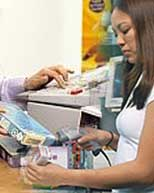 Store Clerk at Cash Register taking inventory with a barcode scanner
